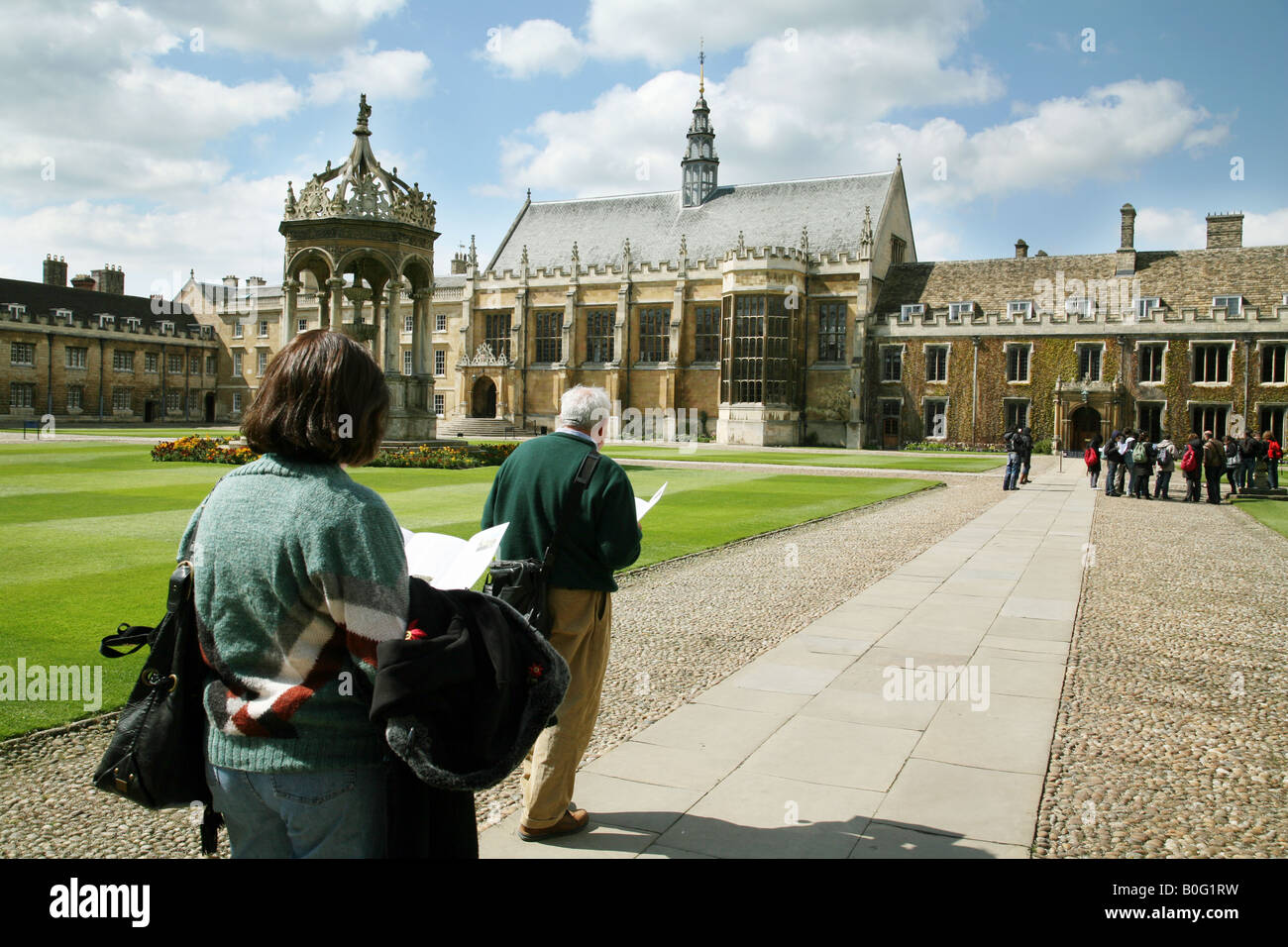 Tourists study a plan of Trinity College, Cambridge University, in the Great Court, with the fountain, hall and - Stock Image