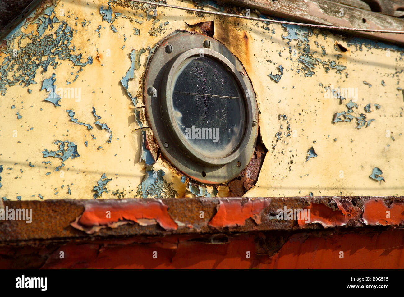 Port hole on an old rusty boat with flacking paint Stock Photo