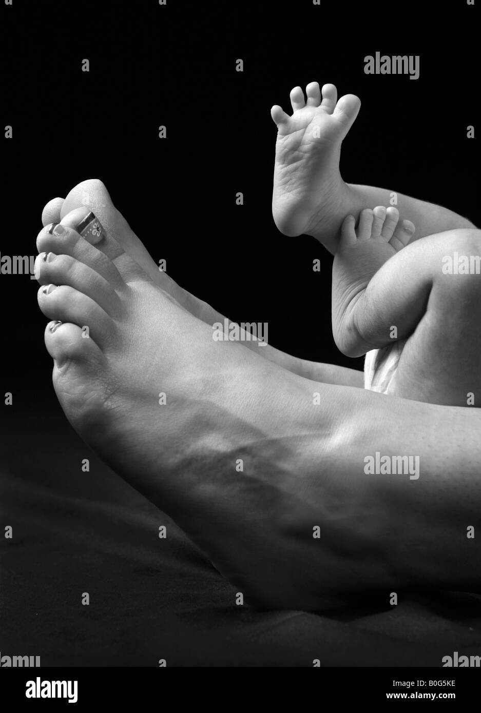 newborn feet together with mothers - Stock Image