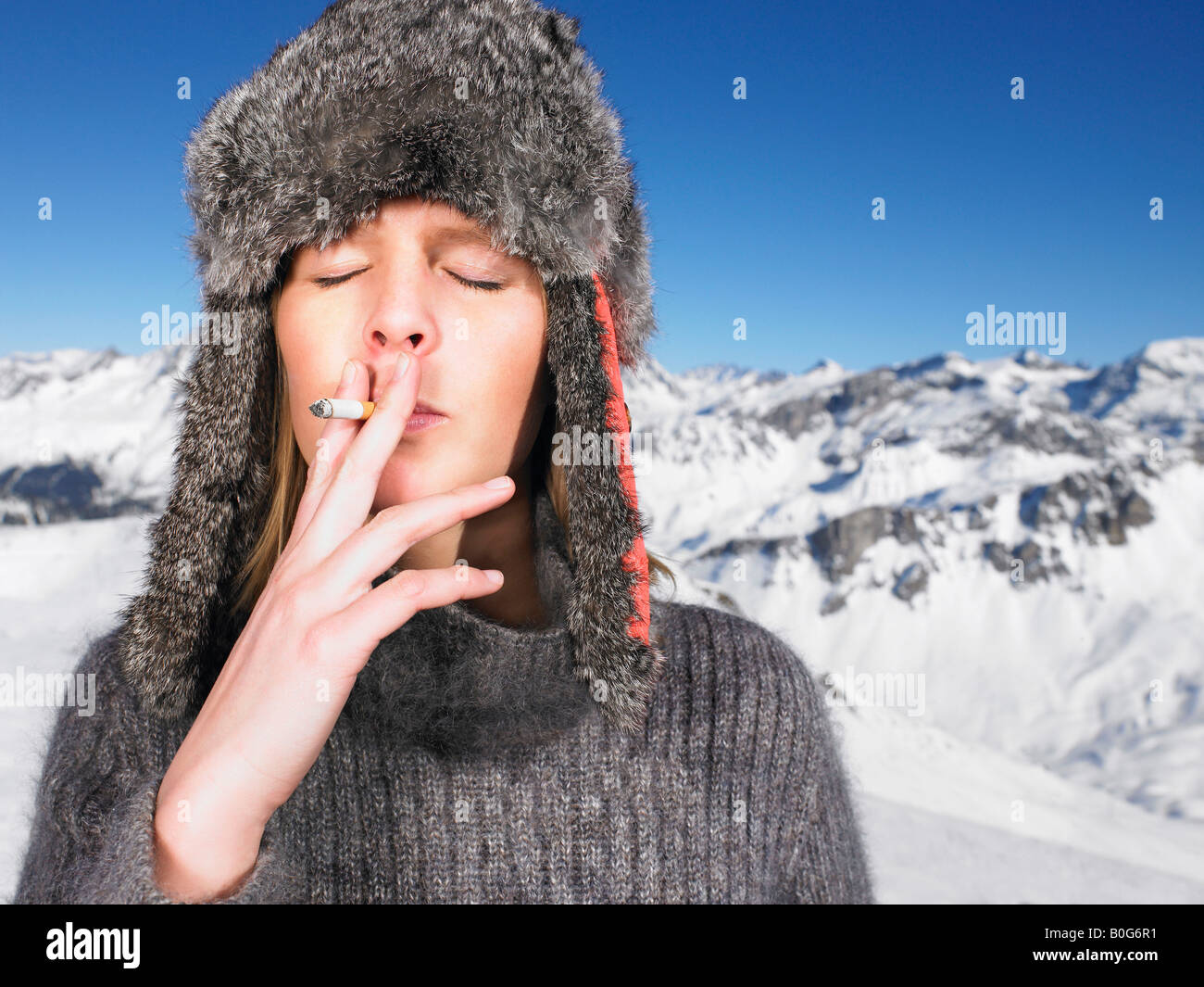 Young woman in hat smoking Stock Photo
