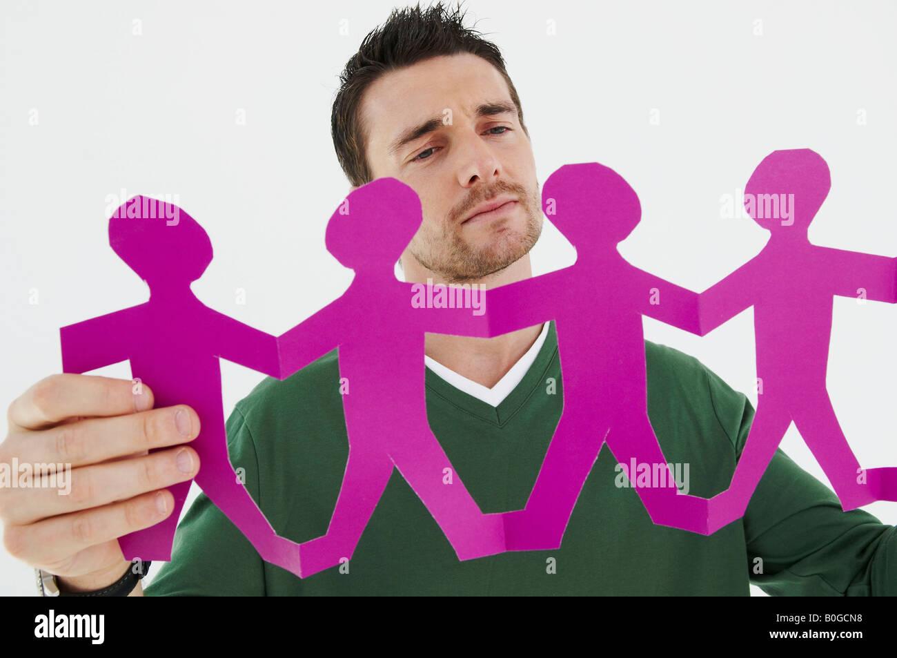 Businessman considers paper figures - Stock Image