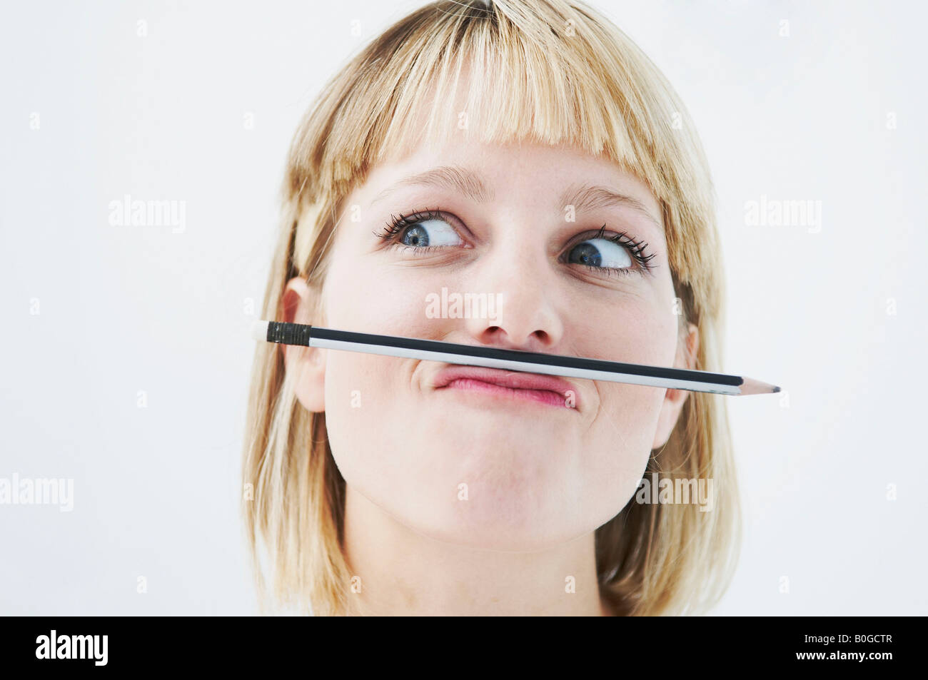 Amusing woman with pencil above mouth - Stock Image