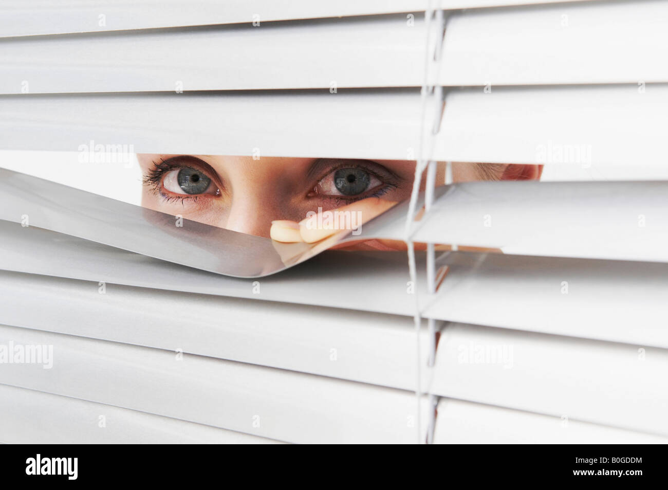Woman looks through blinds - Stock Image