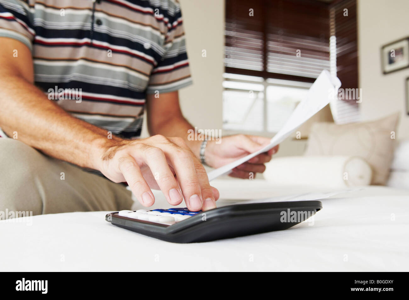 Male's hand adds up bills on calculator - Stock Image