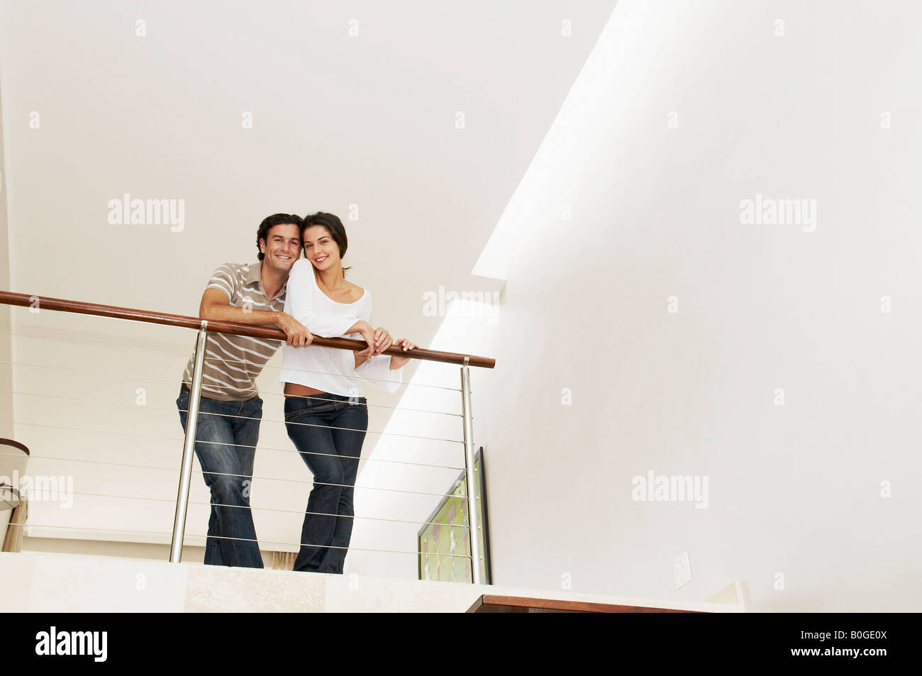 Contented couple lean over balcony - Stock Image
