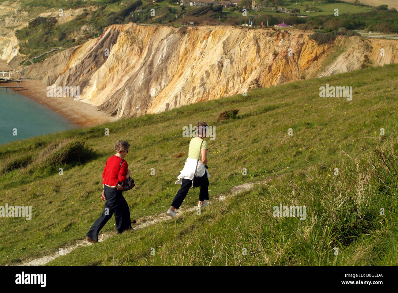 Tourists Walking on Coastal Path and the Coloured Sand Cliffs at Alum Bay Isle of Wight England Stock Photo