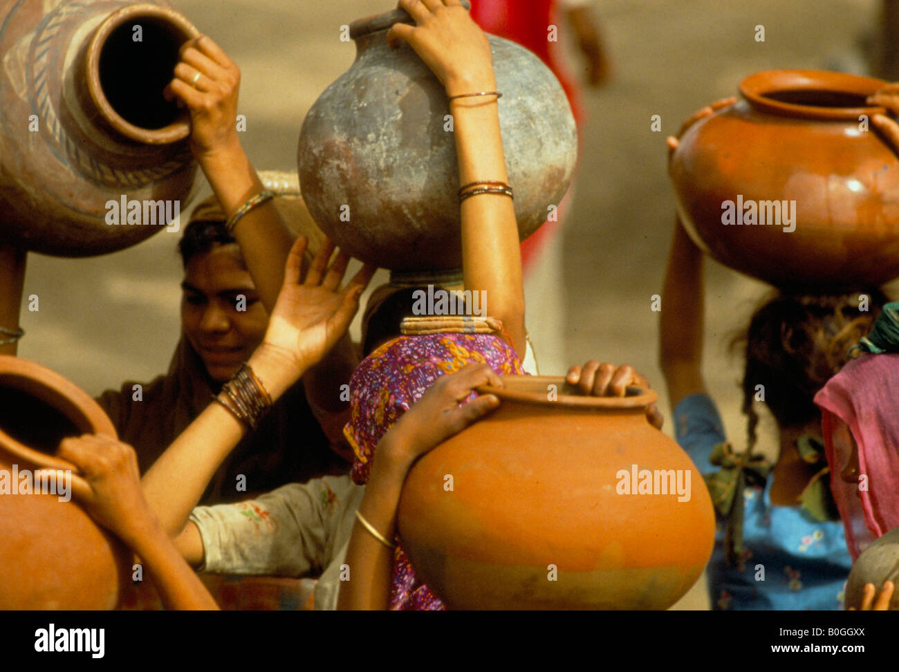 Women carrying water jugs on their heads, India Stock Photo ...
