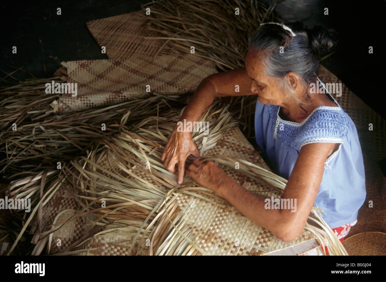An elderly woman weaving palm leaves together to make mats, Tarawa, Kiribati. - Stock Image