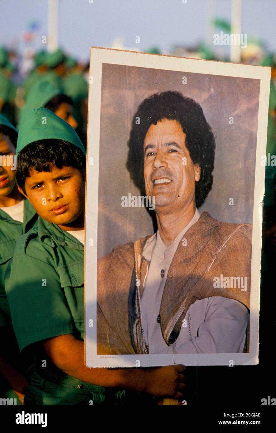 A boy holding a poster of Gaddafi at the 20th anniversary celebration of the revolution, Tripoli, Libya. - Stock Image
