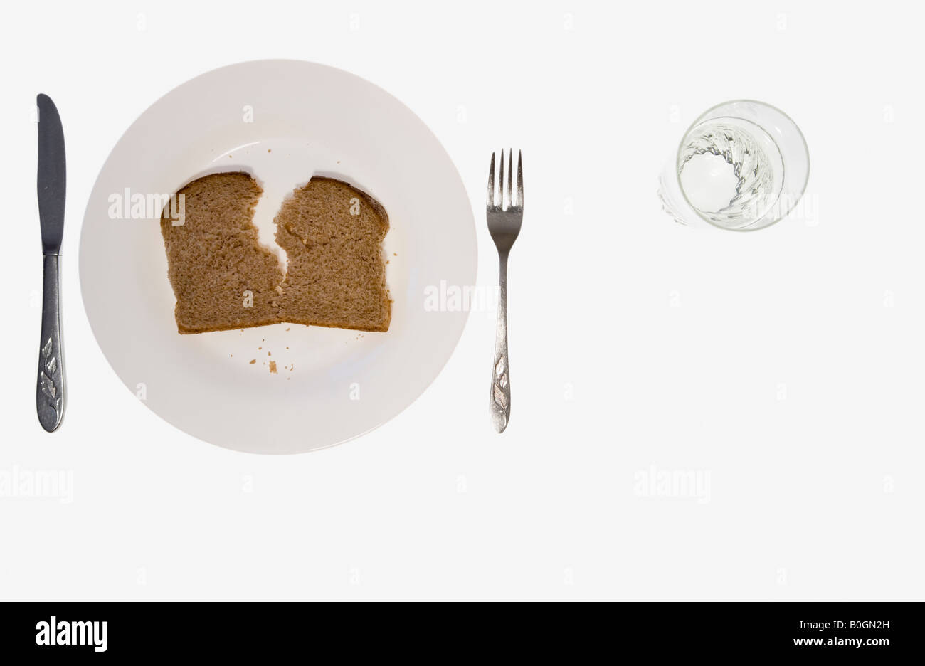 Bread and water with the cutlery positioned for a left handed person - Stock Image