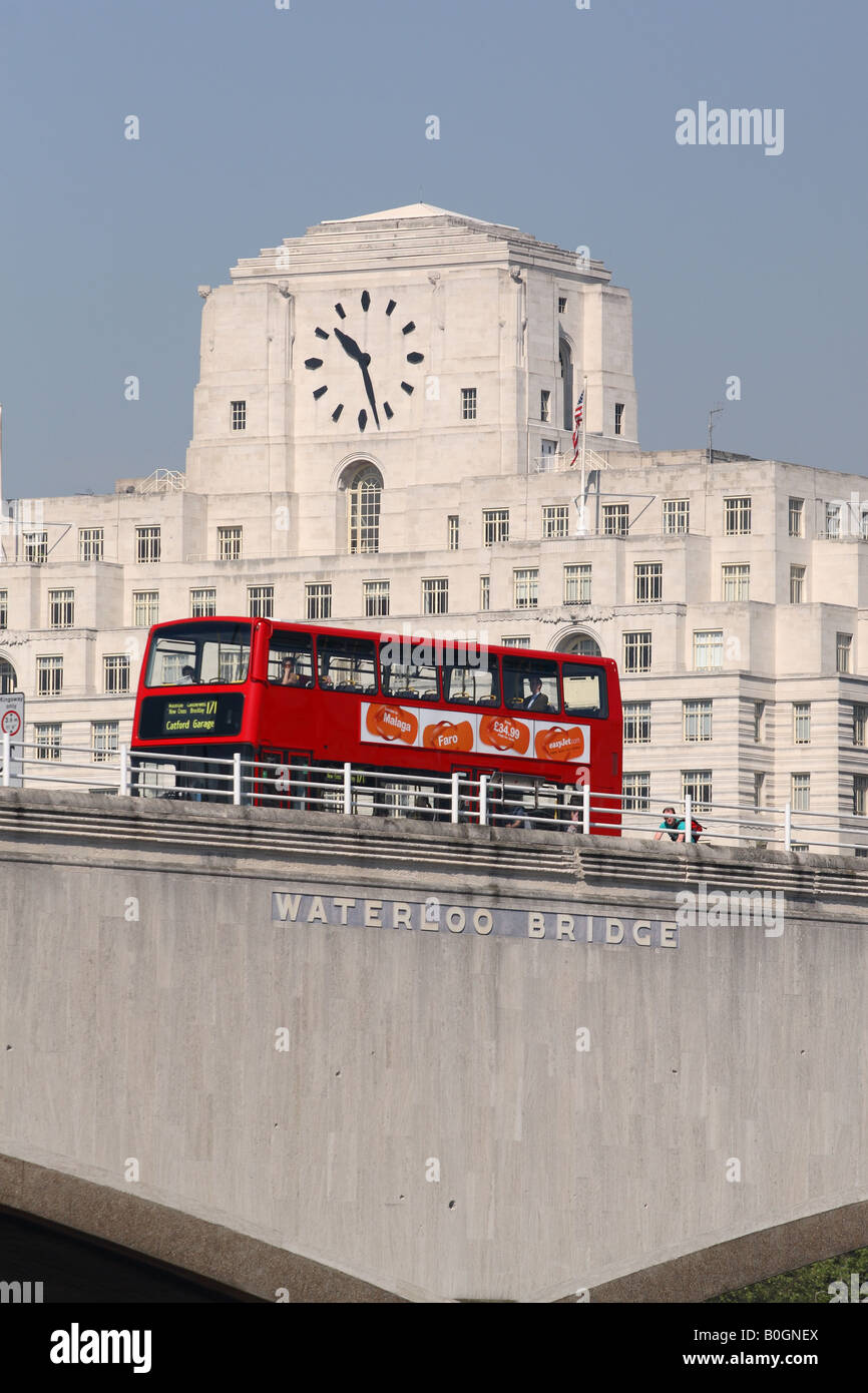 London England a red double decker bus passes over Waterloo Bridge with Shell Mex House behind Stock Photo