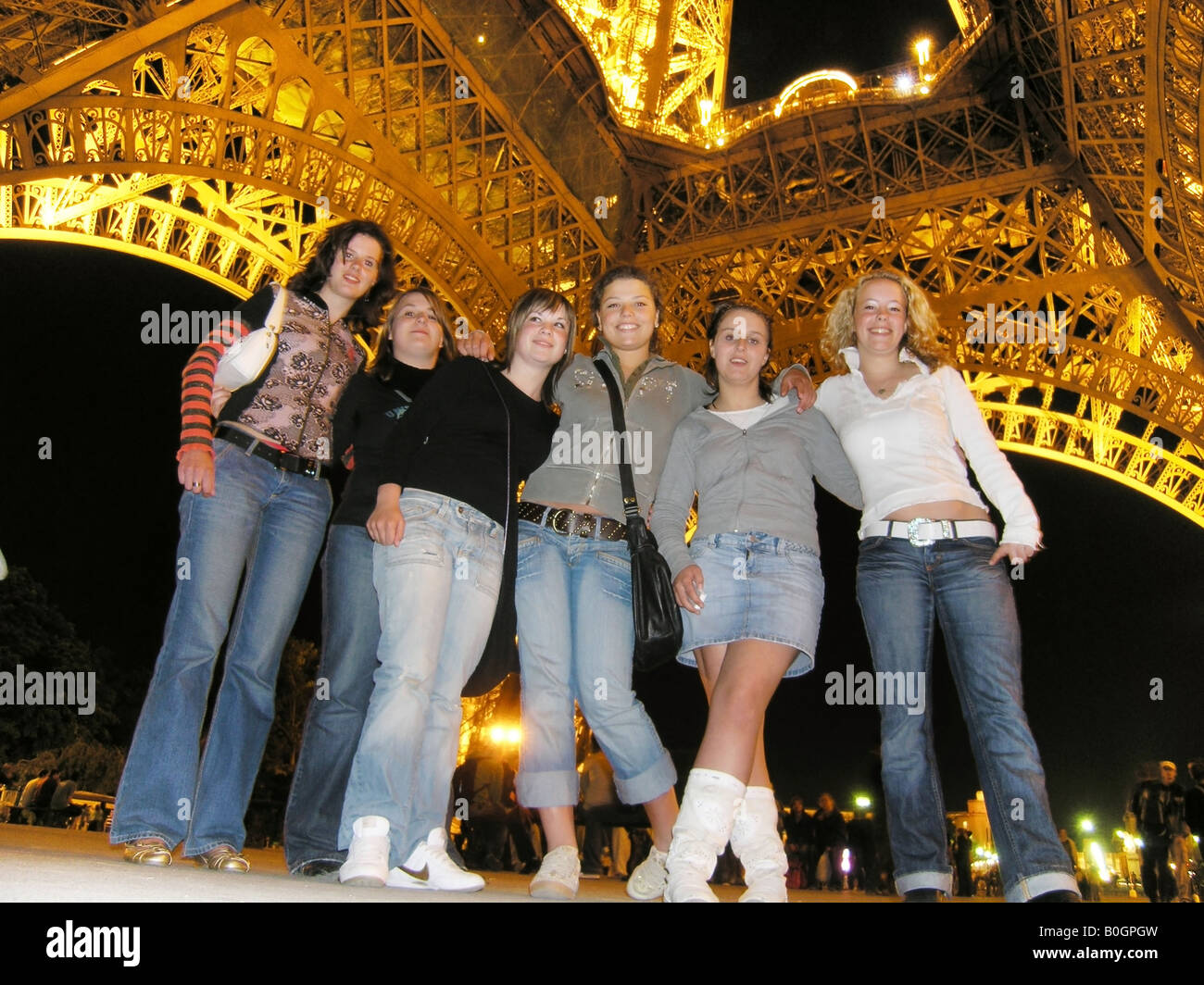 Six teenage students posing under the Eiffel Tower for holiday snapshot - Stock Image