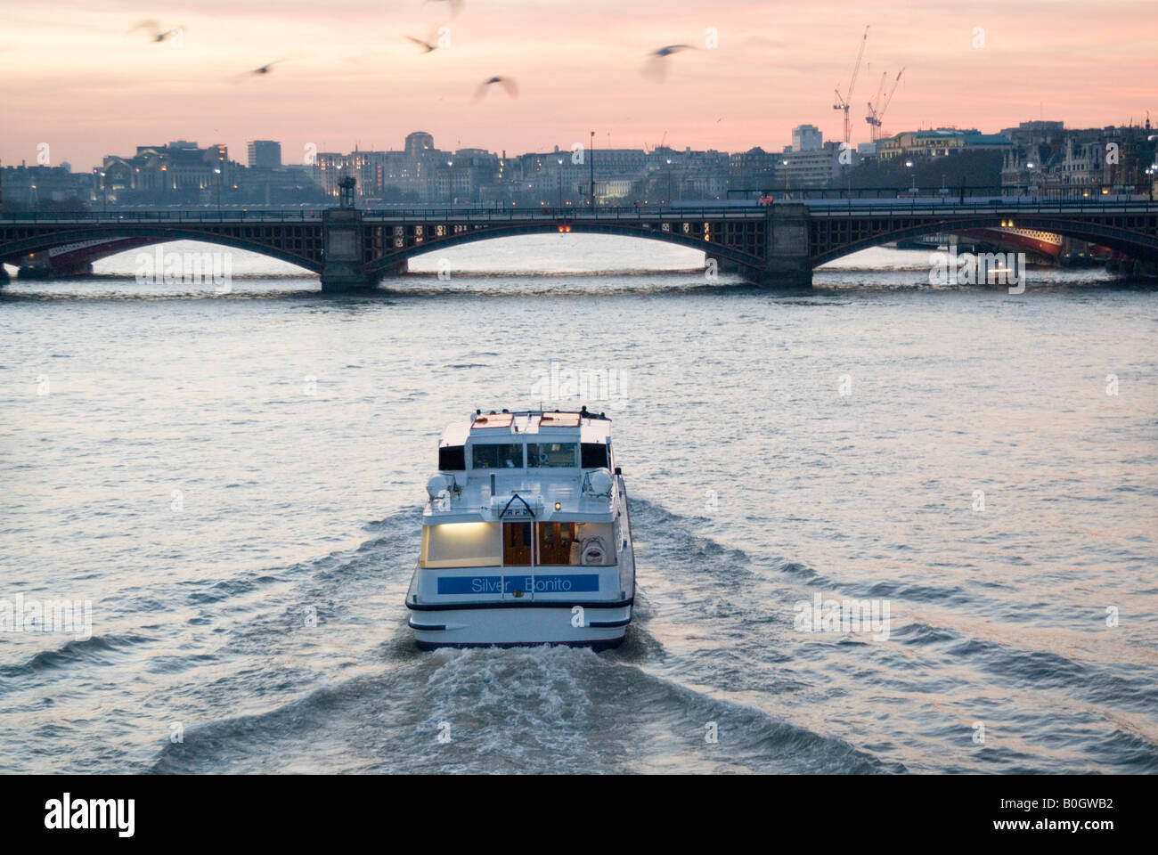Tour boat on the river Thames at dusk, London, England, UK - Stock Image