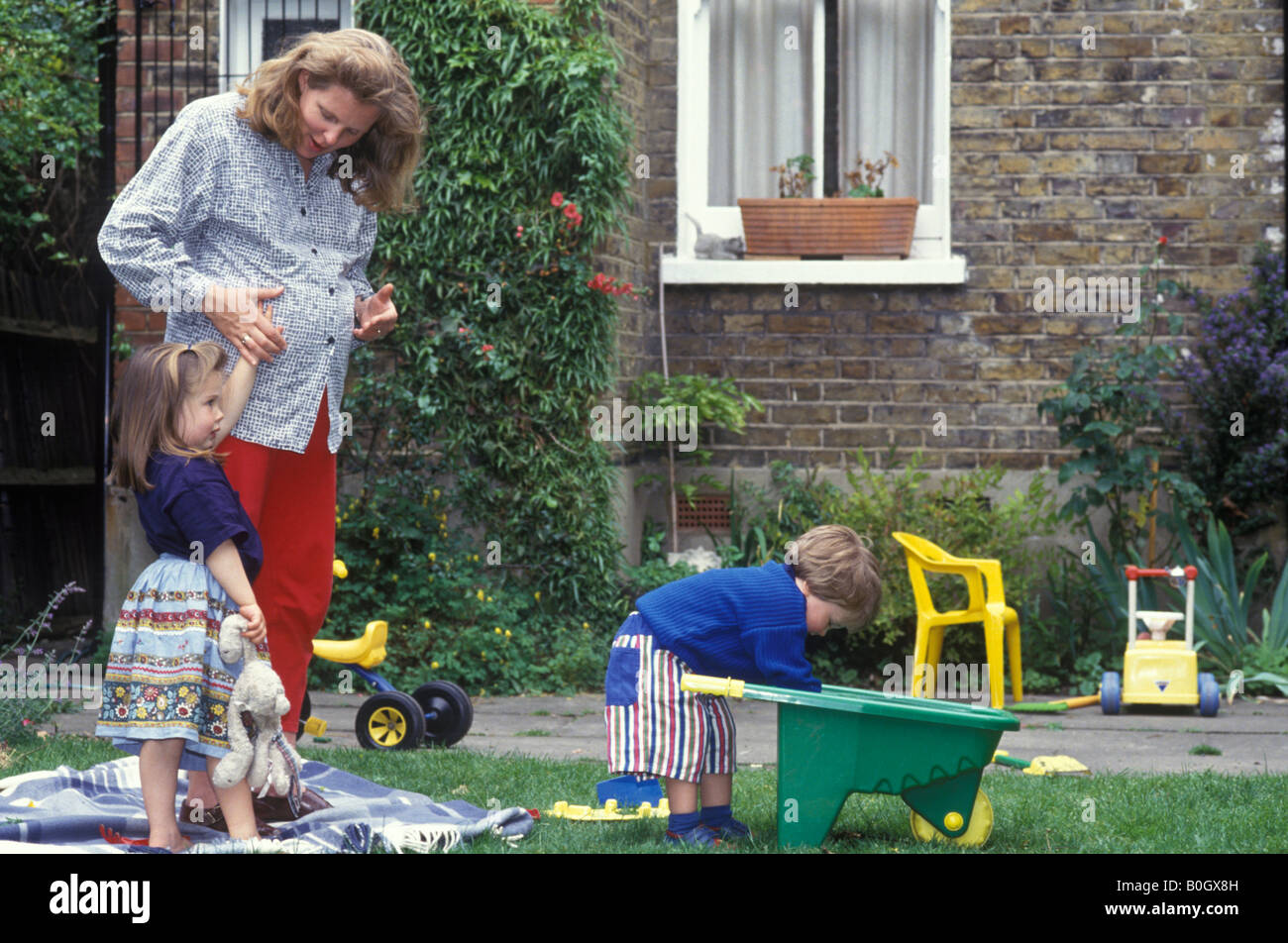 pregnant woman coping with two children in the garden - Stock Image