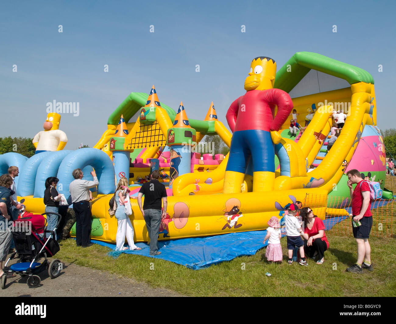 Parents watching their children on an inflatable bouncy castle Stock Photo