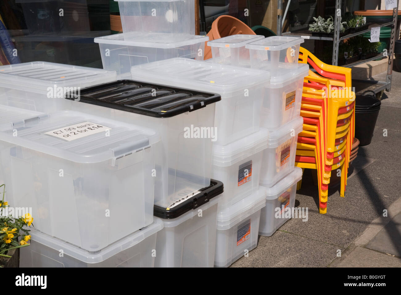England UK Plastic boxes and chairs for sale on display outside shop Stock Photo
