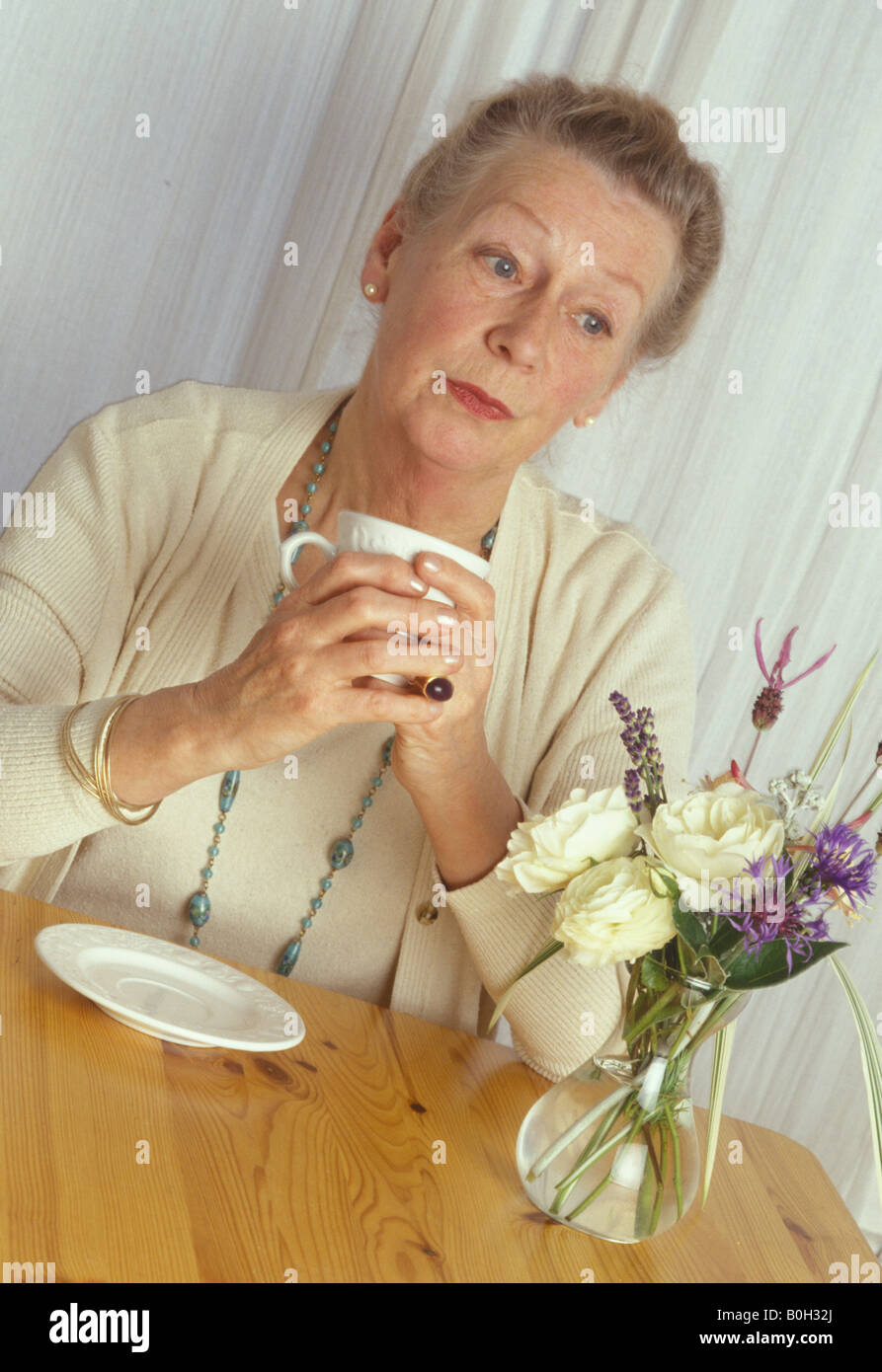 elderly woman drinking tea and looking sad - Stock Image