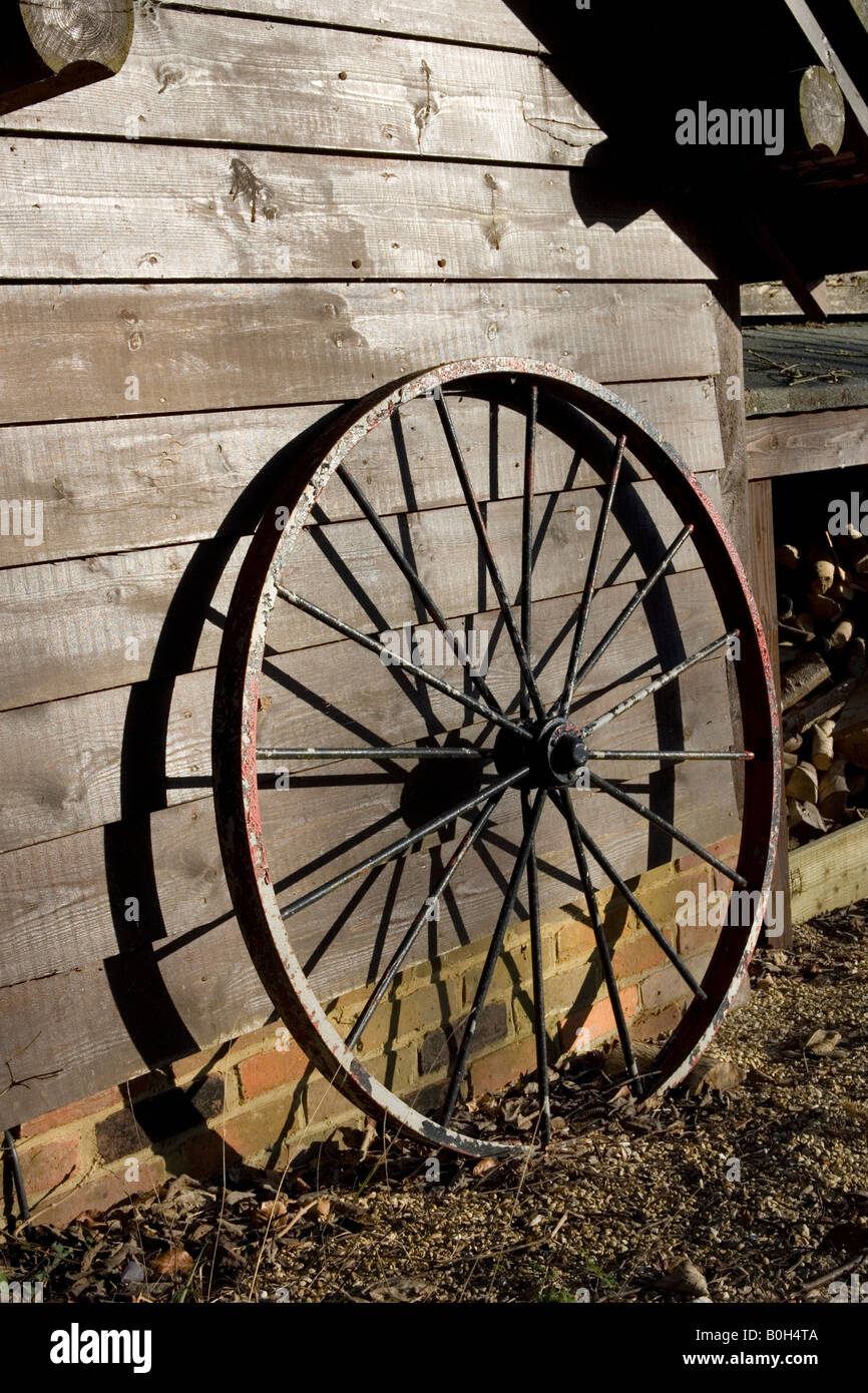 A spoked wheel leans up against a wooden shed. Stock Photo