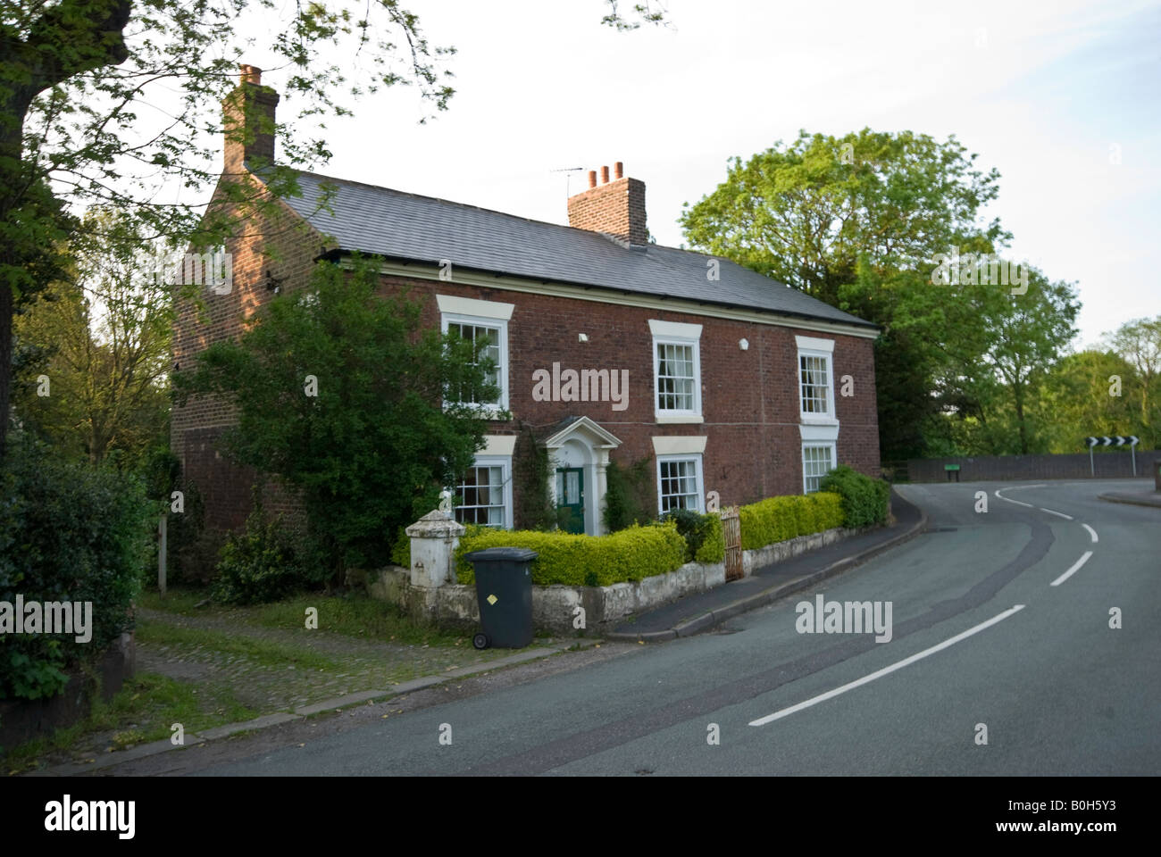 Country cottage on a leafy green road Stock Photo
