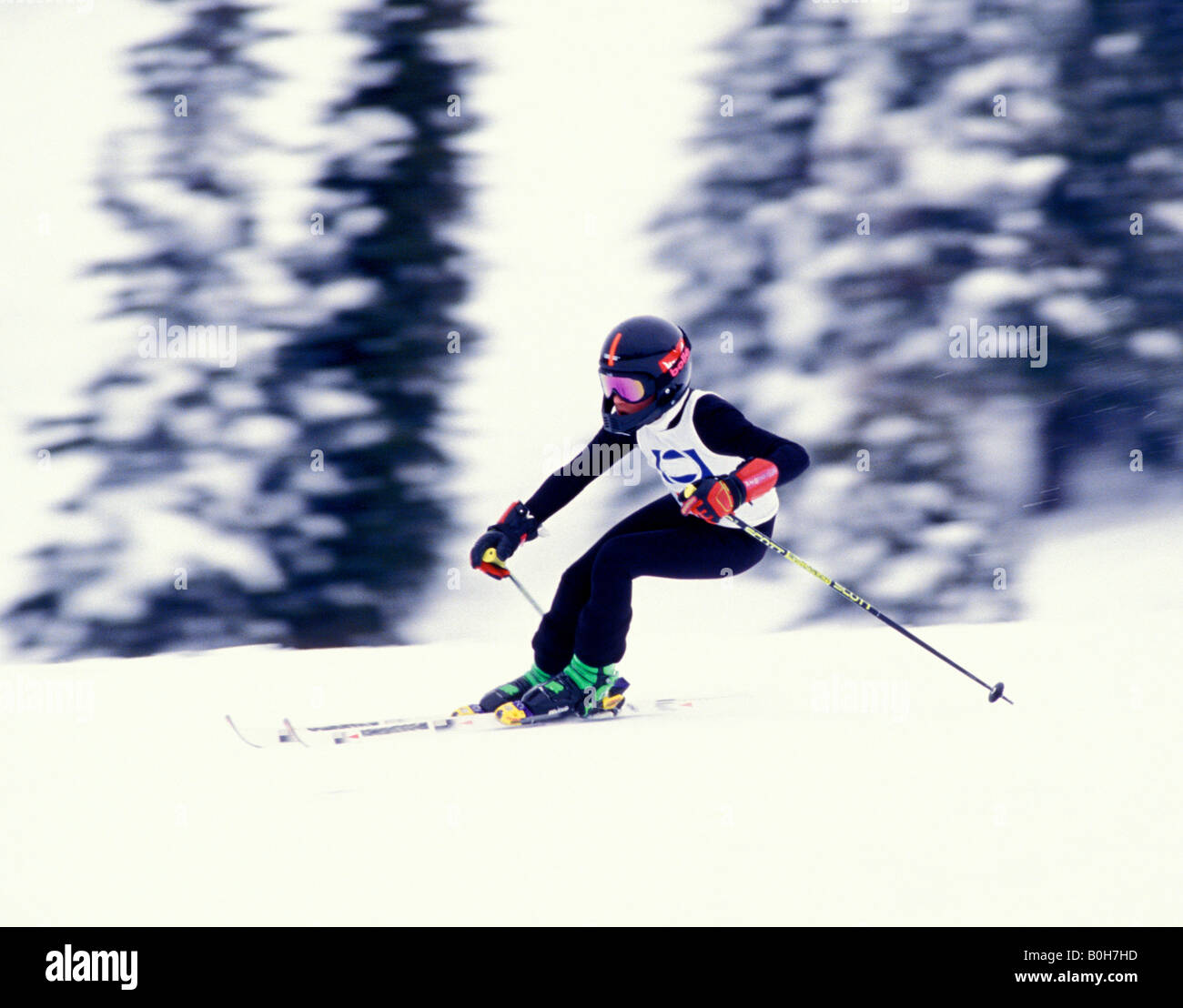 A 14 year old downhill racer speeds through a turn in a race - Stock Image