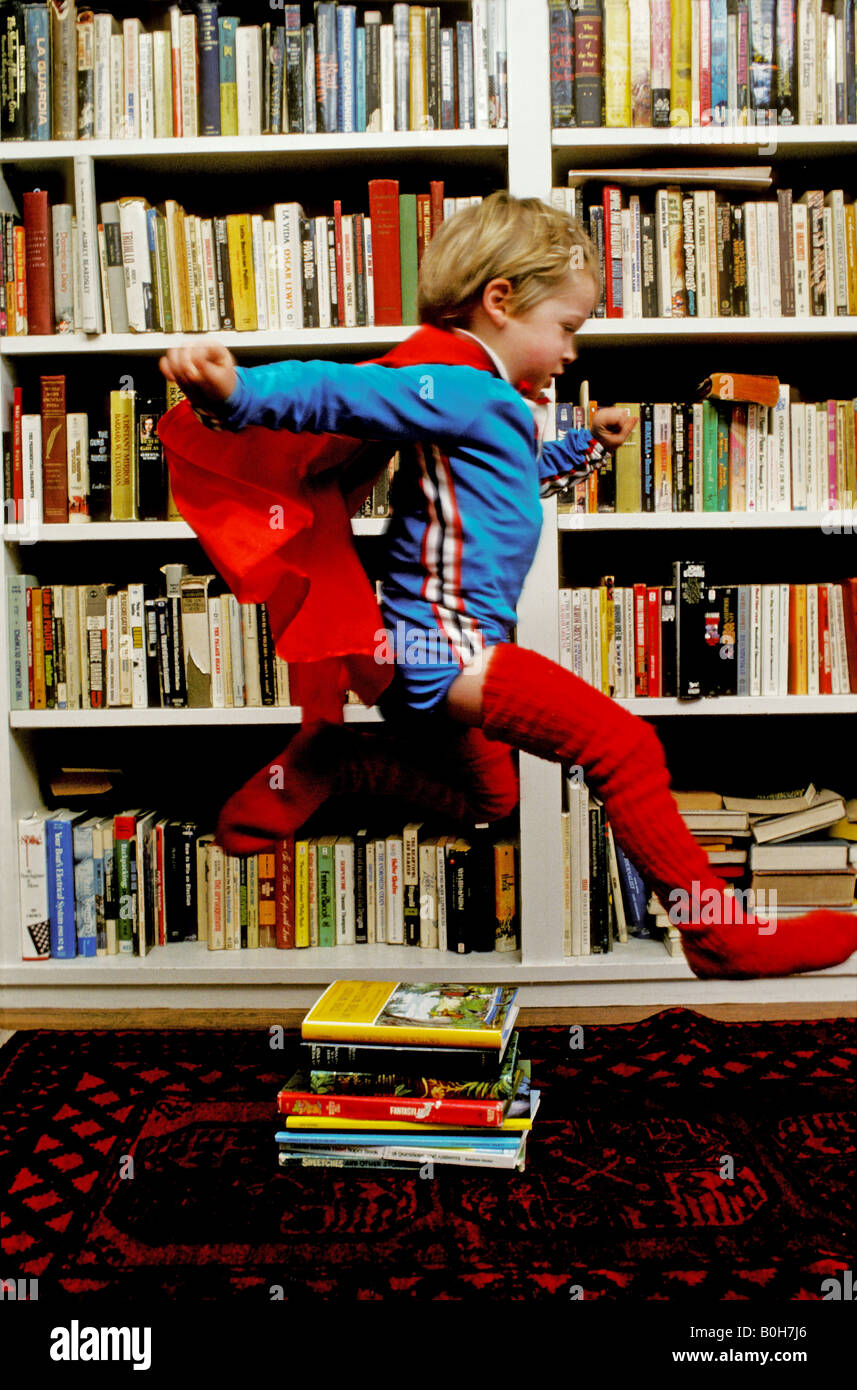 A three year old boy wearing a cape and matching leggings leaps over a stack of books as he pretends to be Superman - Stock Image