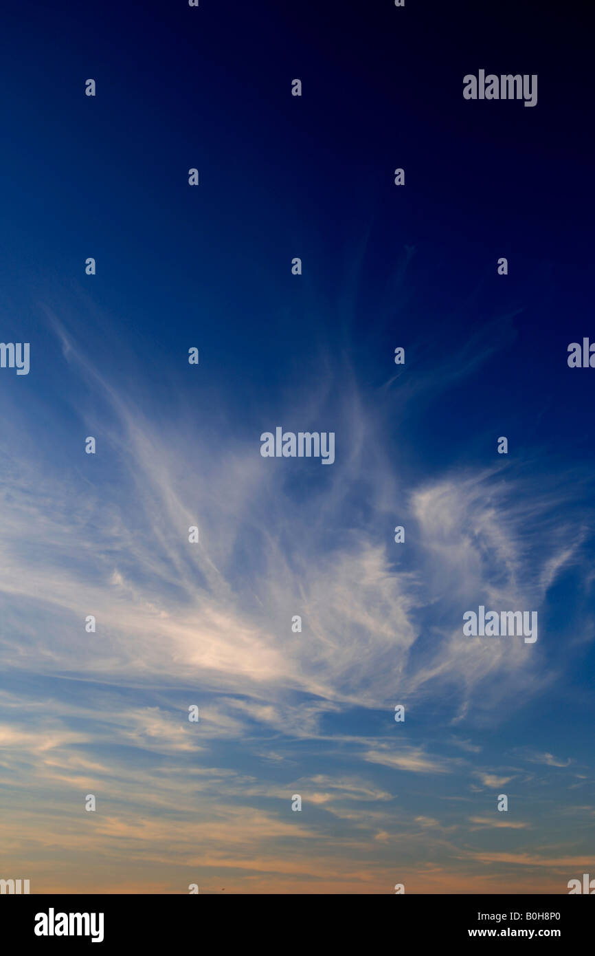 Winter Cirrus Uncinus trail clouds in a deep blue polarised sky - Stock Image