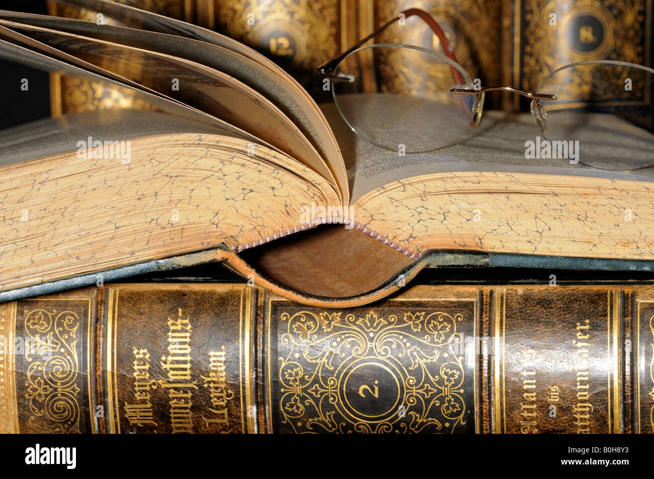 Reading glasses resting on an open page of an old encyclopaedia, leather bound books - Stock Image