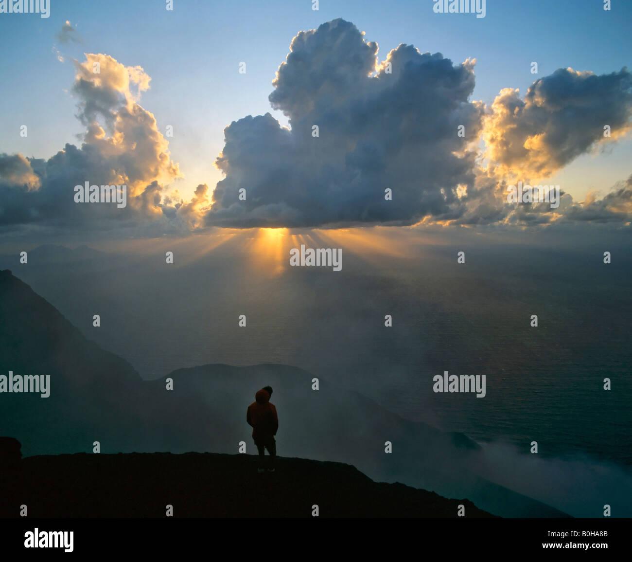 Peak of Stromboli Volcano, man standing in backlight, sunbeams, rays of sunlight, Aeolian Islands, Sicily, Italy Stock Photo