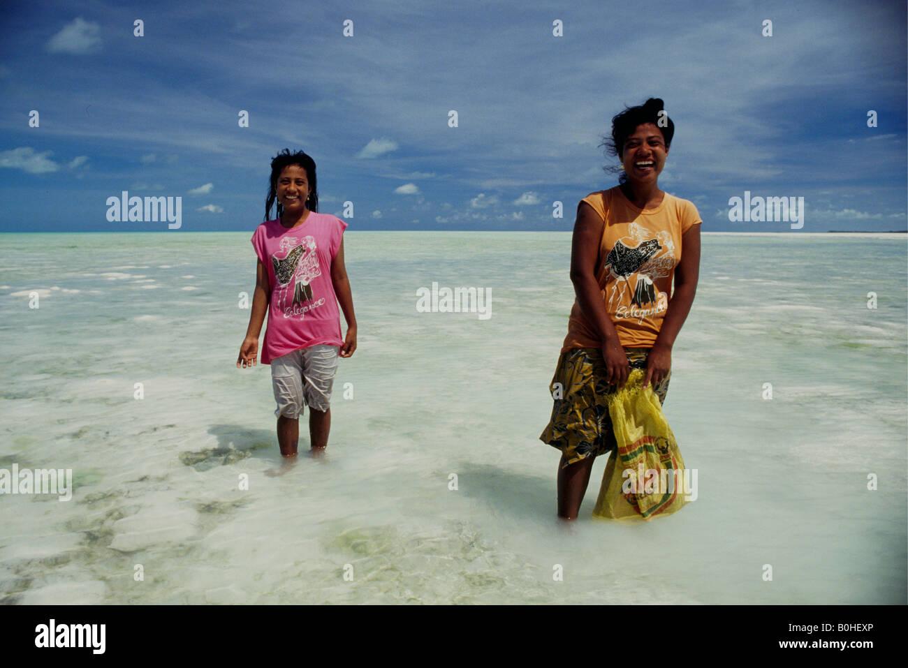 Women searching for shellfish in a lagoon, Tarawa, Kiribati. - Stock Image