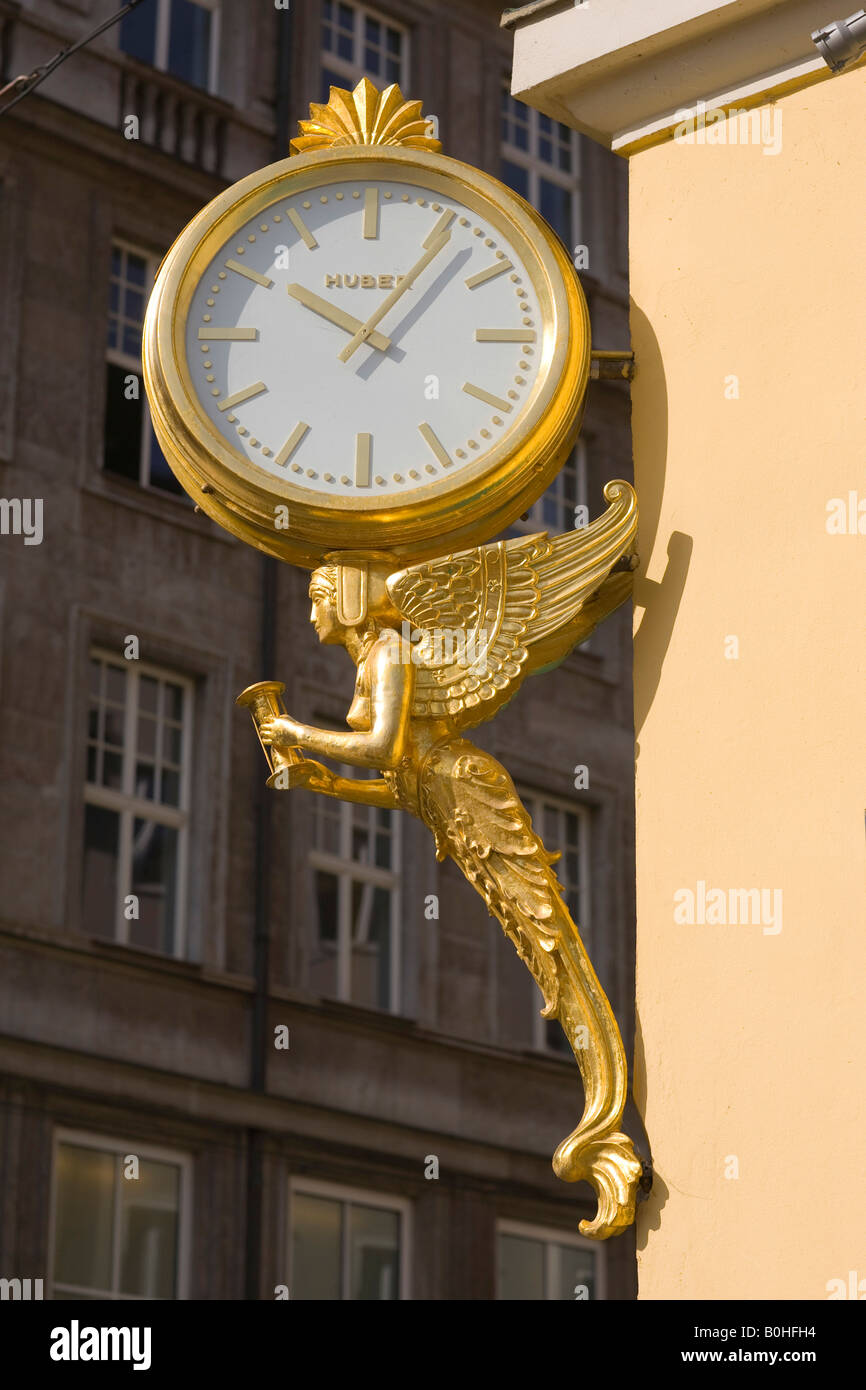 Gilt angle holding a hourglass supporting a clock, shop sign of the Huber-Juwelier jewellery shop on the Residenzstrasse, - Stock Image