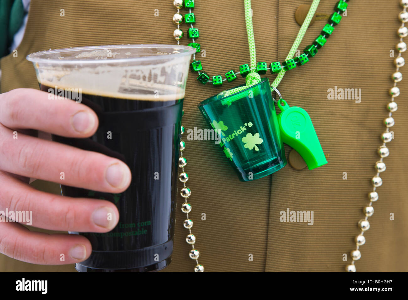 Drinker celebrating St Patrick's Day with a Guinness. - Stock Image