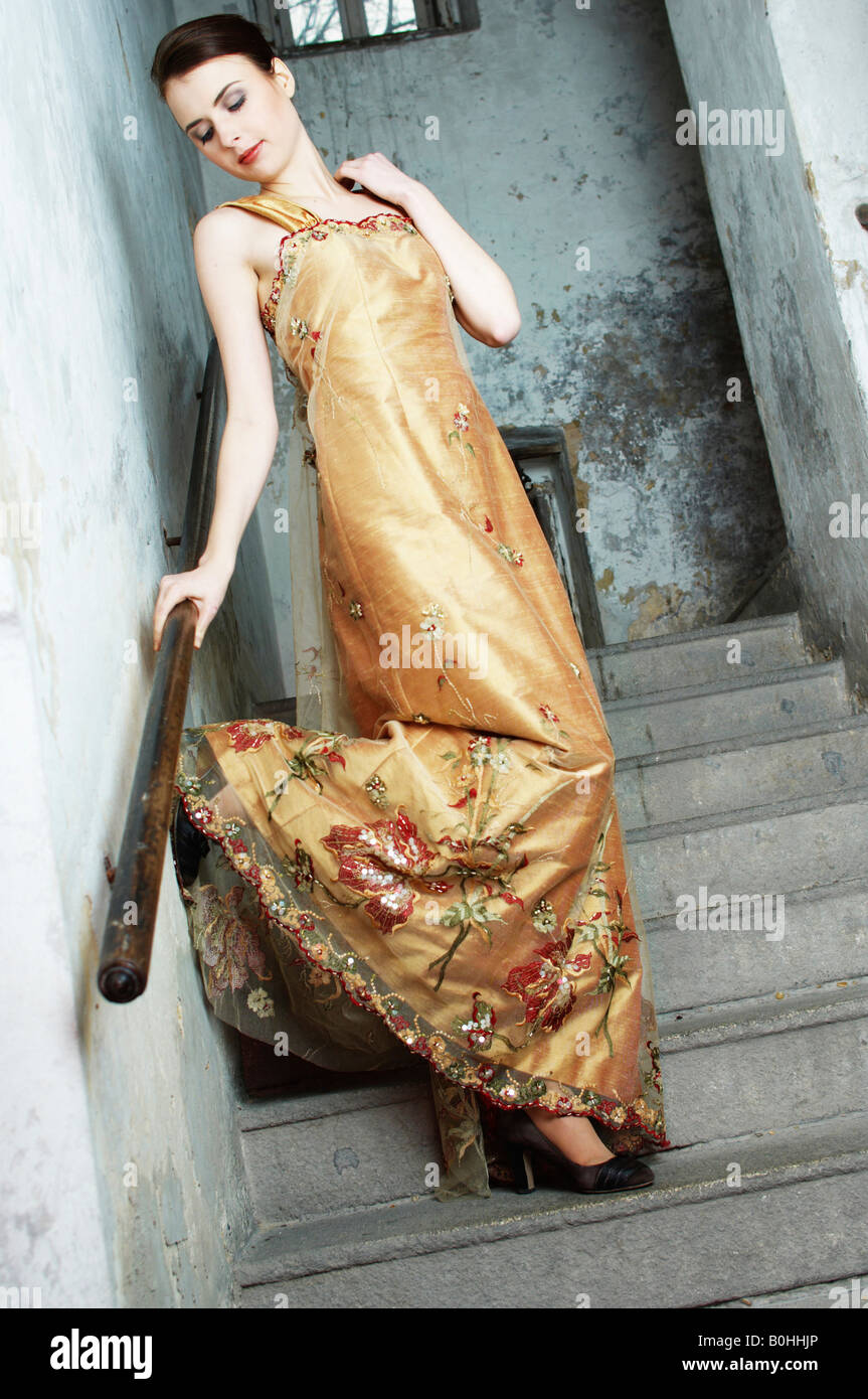 Young woman wearing an evening gown, standing in a staircase Stock Photo