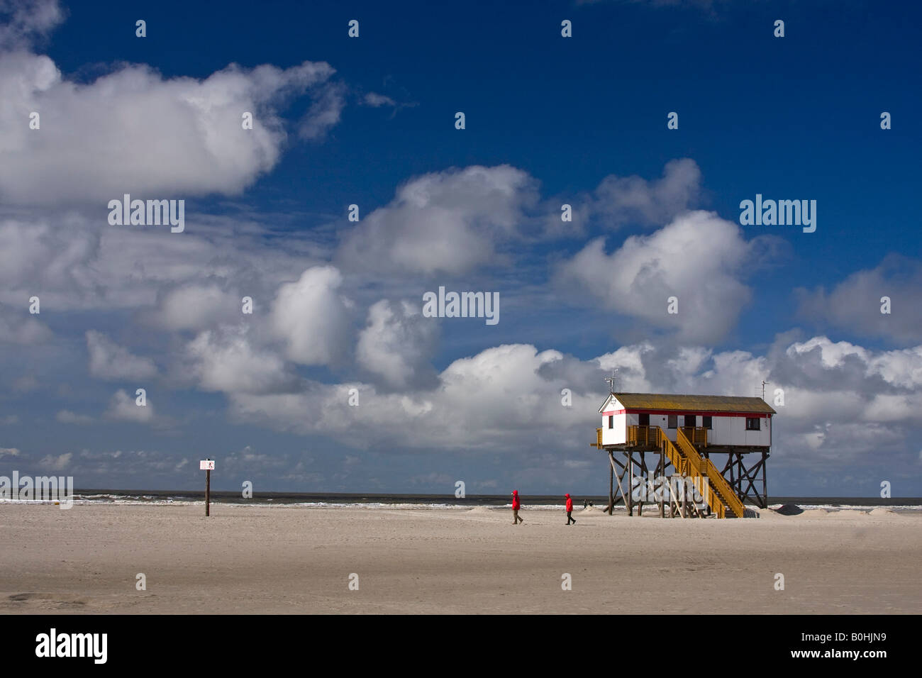 People walking past a house on stilts on the beach at the seaside resort of St. Peter Ording, North Sea coast, North Stock Photo