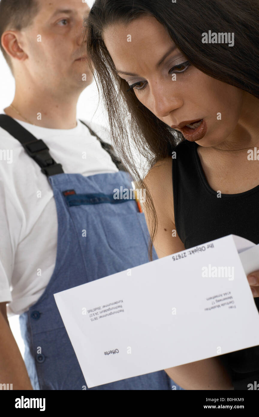 Woman shocked, appalled at the estimate given to her by a handyman, workman (back) - Stock Image