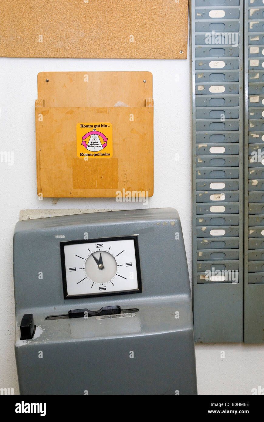 Tilted attendance recorder (time punch clock) showing five minutes to twelve o'clock, 5 to 12, next to an empty - Stock Image