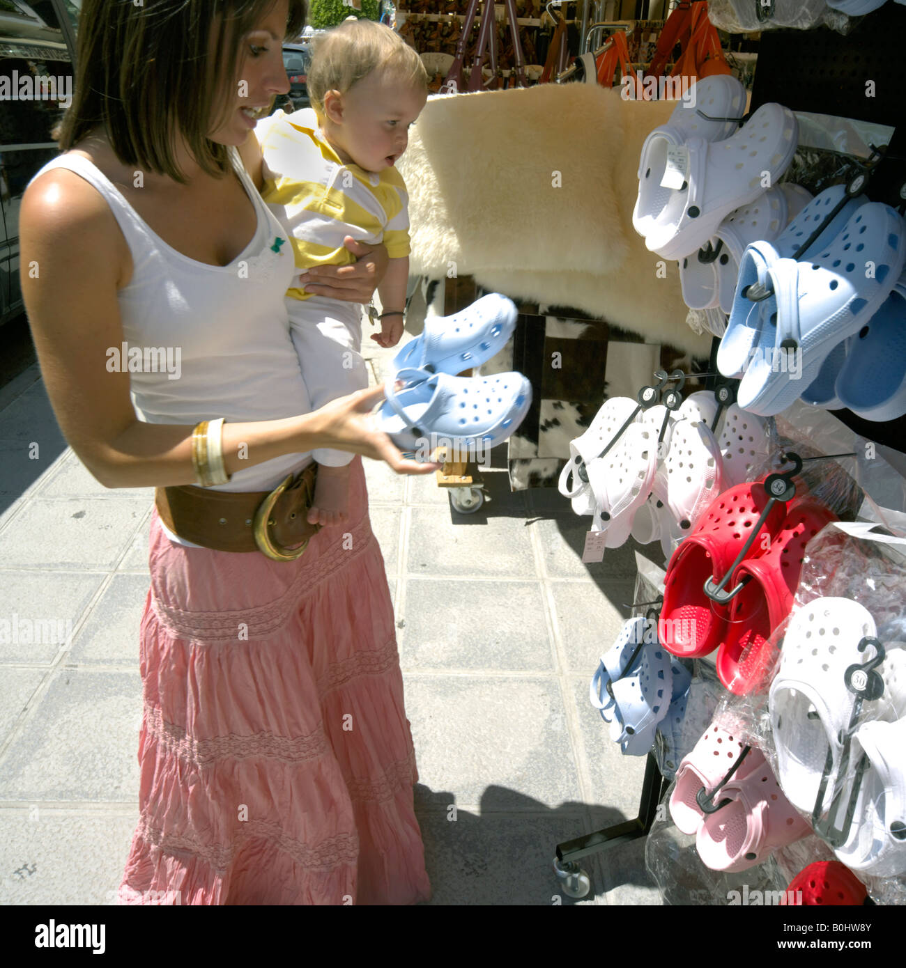 Mother and toddler shopping for ugly croc plastic shoes, Mijas Pueblo, Costa del Sol, Andalucia, Spain - Stock Image