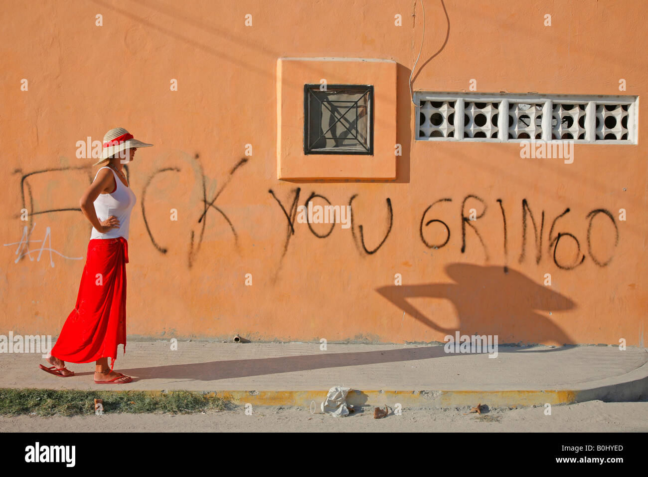 Tourist walking past a bit of anti American grafitti on a wall in Playa del Carmen Mexico - Stock Image
