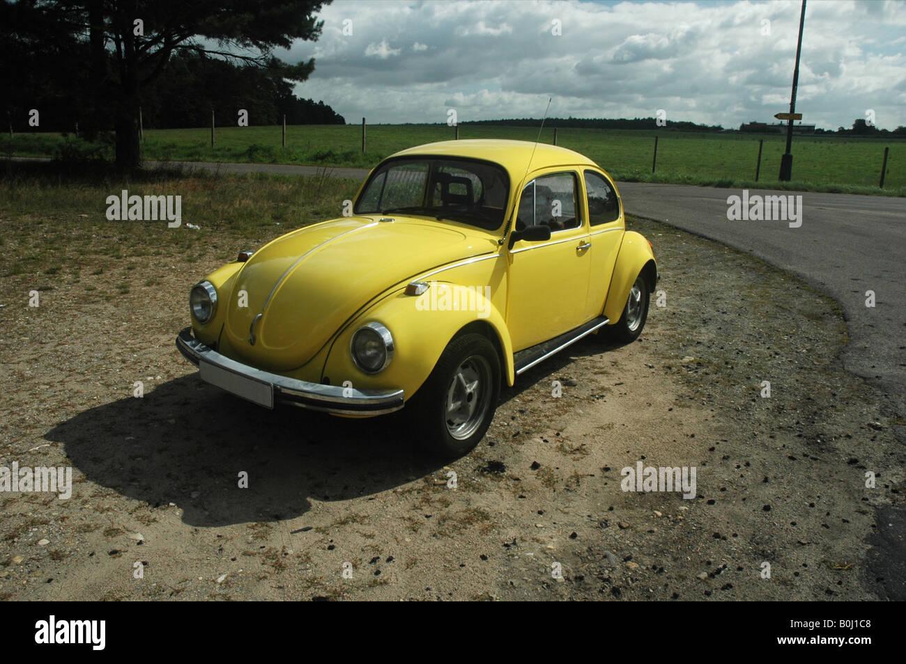 yellow VW beetle 1302 on sandy ground - Stock Image