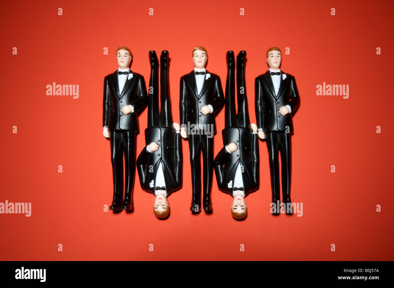 Five plastic men in tuxedos on a red background - Stock Image