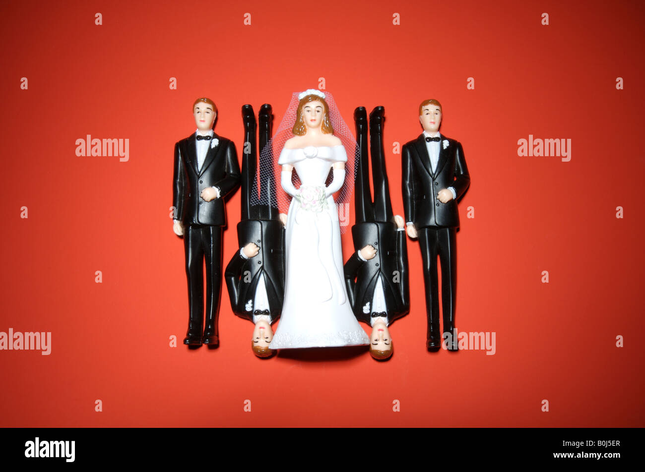 A plastic wedding bride and four men in tuxedos on a red background - Stock Image