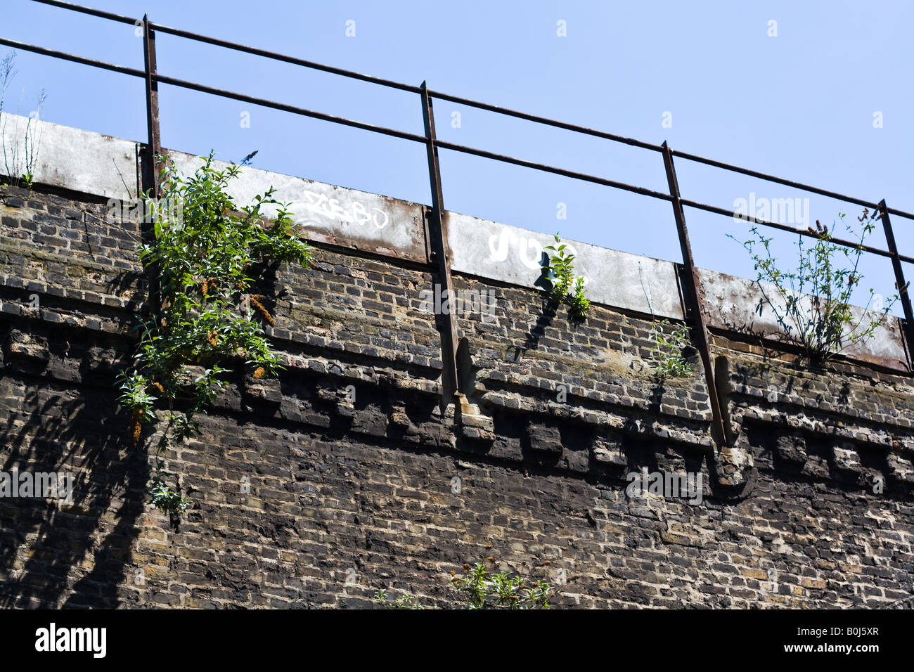 Looking up at old brick railway bridge with railings, some plants growing out of wall and faint graffiti. - Stock Image