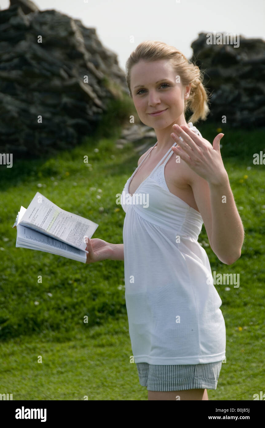 Young pretty blonde intelligent clever woman student at Aberystwyth university rehearsing a play outdoors,  summer - Stock Image