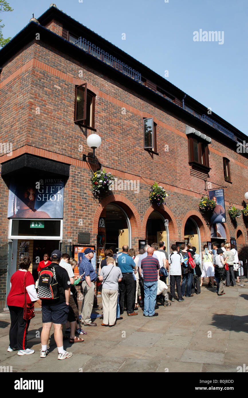 tourists queuing to enter the jorvik viking centre sign coppergate shopping centre york north yorkshire england - Stock Image