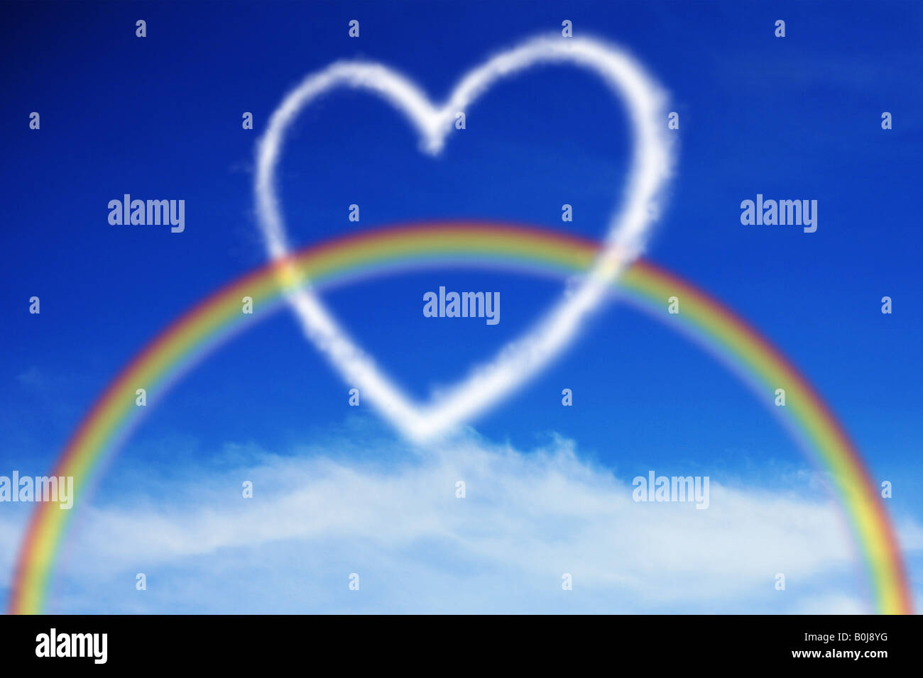 Rainbow going trough a heart shaped cloud in the bright blue summers sky - Stock Image