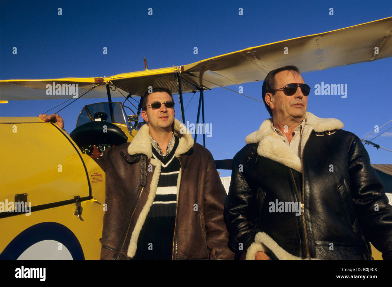 Two pilots with flying jackets near old trainer biplane De Havilland DH 82c Tiger Moth - Stock Image