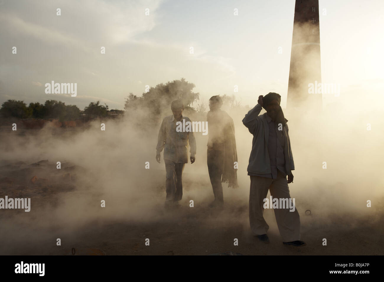 Men walking through the smoke from a brickworks in Rajasthan India - Stock Image
