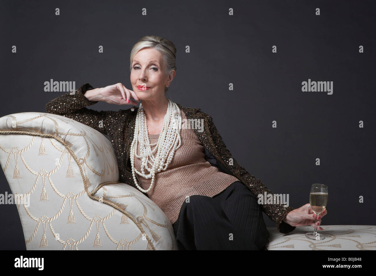 Mature Woman Having Glass of Champagne - Stock Image
