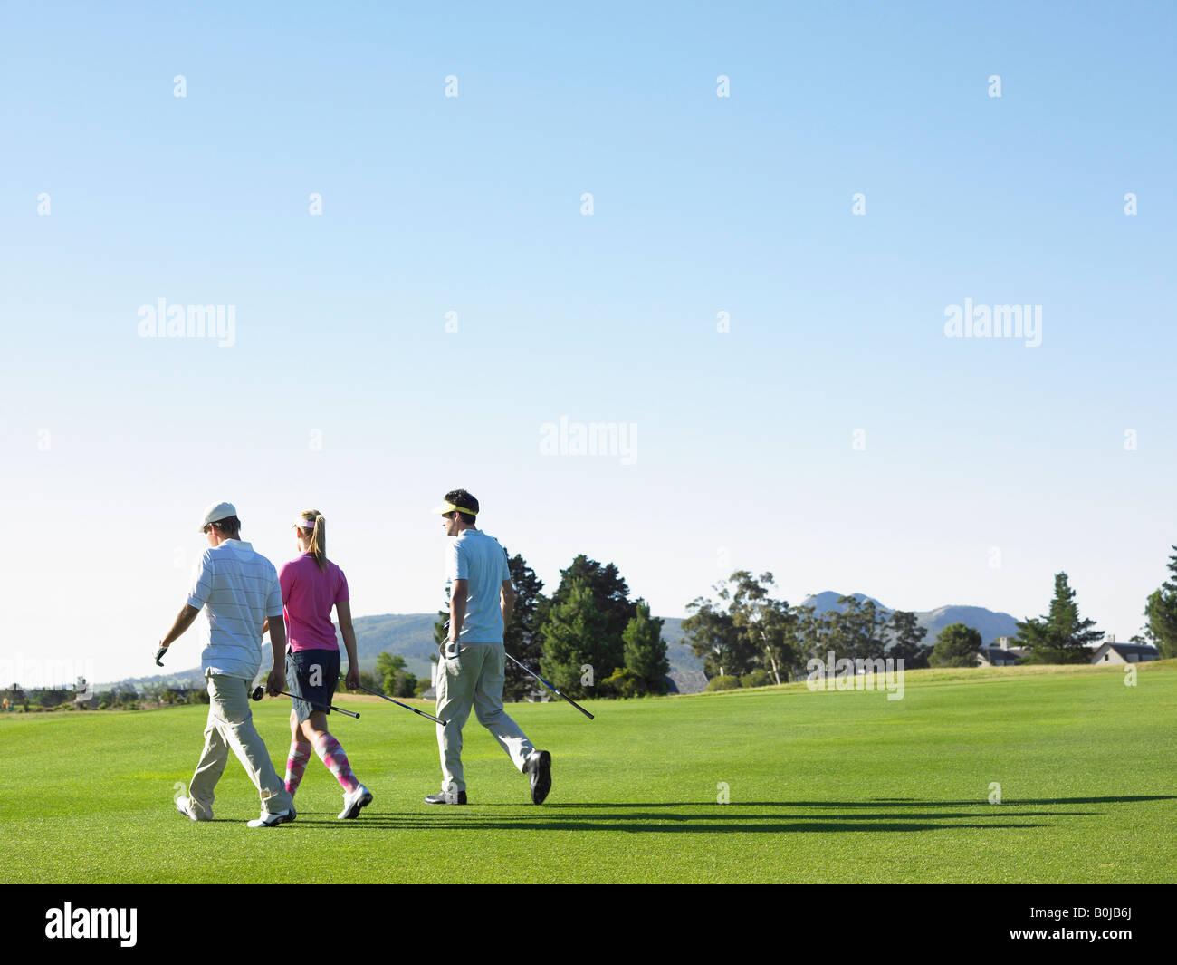 Three Golfers on Course - Stock Image