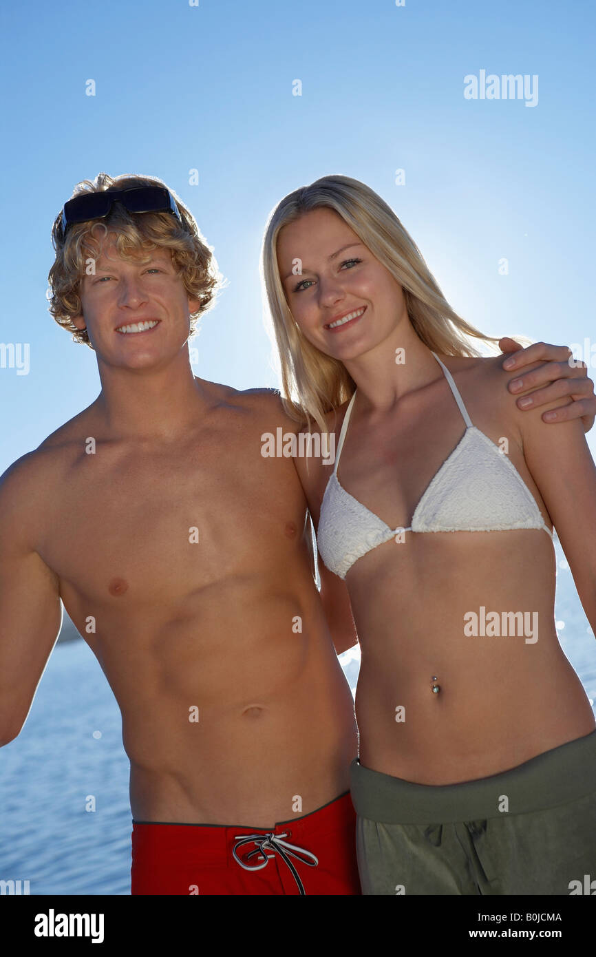 Young couple in swimwear outdoors, portrait - Stock Image