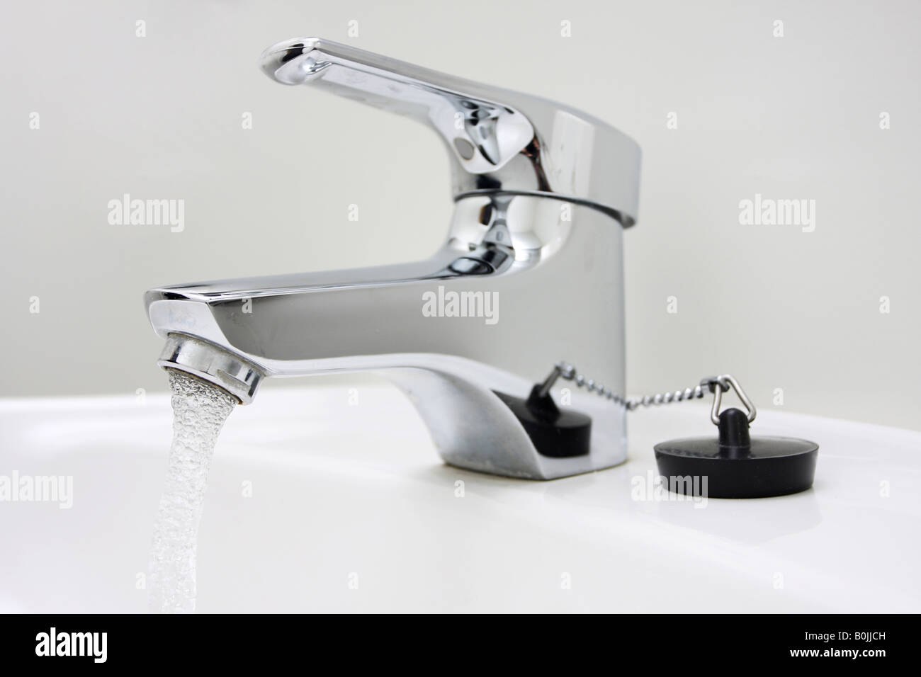 chrome faucet on a sink running water - Stock Image